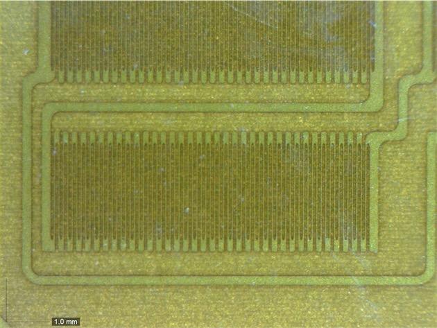 Les jauges de déformation, aussi appelées extensomètres à fils résistants, vues au microscope. Les spires mesurent à peine quelques micromètres d'épaisseur. Leur déformation sous la pression modifie la résistance électrique du circuit : lorsqu'elles sont étirés, la résistance augmente;lorsqu'elle sont compressées, la résistance diminue. Les «boutons » PagePress du Kindle Voyage utilisent la même technologie. Image iFixit.