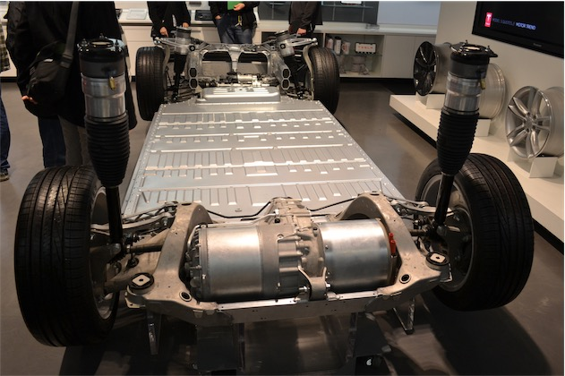 Le châssis d'une Model S, conçue par Tesla : si on enlève les quatre roues, les deux moteurs au premier plan et les amortisseurs, il ne reste que la batterie. Celle-ci occupe l'essentiel de l'espace et représente la majorité de la masse du véhicule. (Photo Oleg Alexandrov CC BY-SA 3.0)