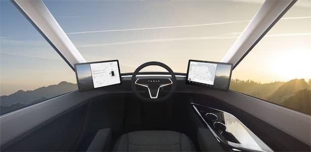 La cabine intérieure ressemble davantage à un poste de conduite de train. Le conducteur est en position centrale pour maximiser la place, le confort et la sécurité. À noter que le volant et les deux écrans proviennent de la Model3. Cliquer pour agrandir