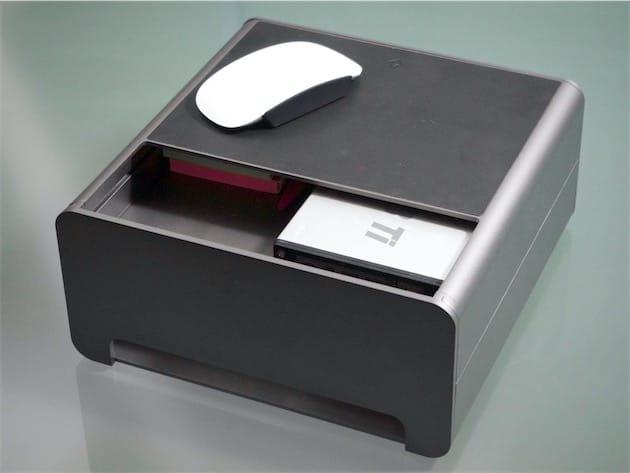La large ouverture à l'arrière, par laquelle passe le pied de l'iMac…et la poussière. Le plateau supérieur est recouvert de cuir, et peut accueillir une souris et un grand smartphone. L'ouverture du bas permet de faire passer les câbles.