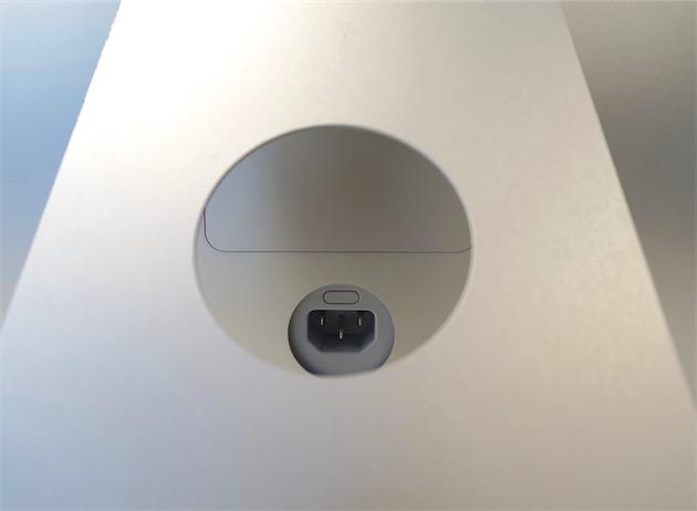 Derrière le pied, la trappe permettant d'accéder à la RAM. On ne peut y accéder sans débrancher la machine : le bouton permettant de la déverrouiller se cache derrière le cordon d'alimentation. Une mesure de sécurité qui n'en a pas l'air.